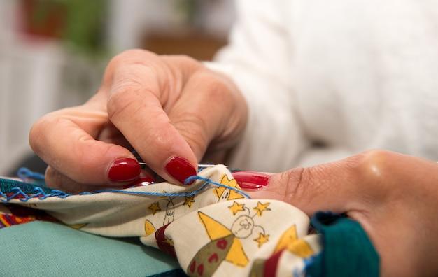Женщина руки шить для отделки стеганое одеяло.