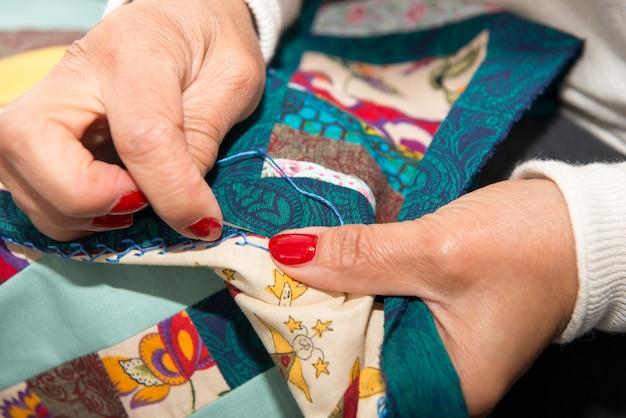 Женщина шьет для отделки стеганое одеяло.