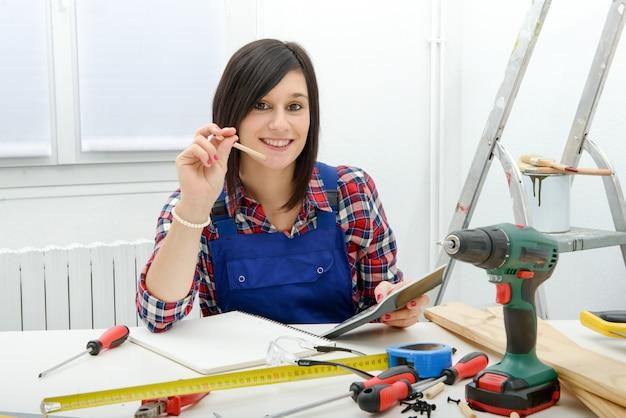 彼女のワークショップで机に座っている女性大工