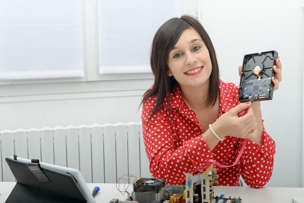 ブルネットの女性技術者はコンピューターを修理します