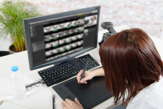 Молодая женщина-дизайнер с помощью графического планшета