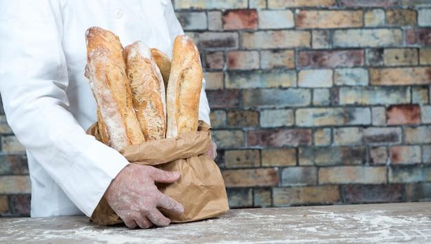 Бейкер держит традиционные хлебные французские багеты