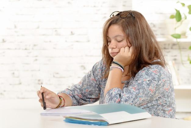 Студентка, в очках, делает домашнее задание