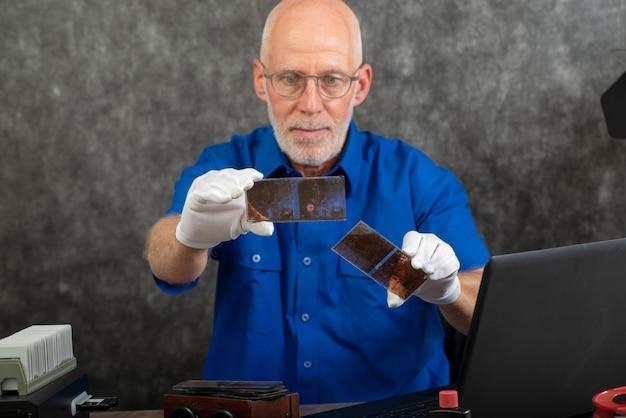 ガラス板上の古い写真をデジタル化する白い手袋を持つ技術者