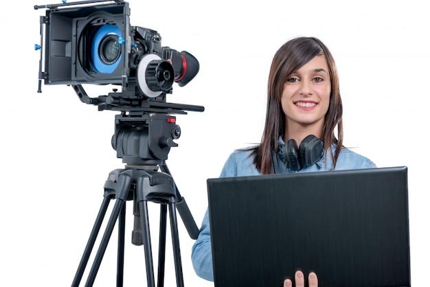 Видео редактор молодой женщины работая с компьтер-книжкой