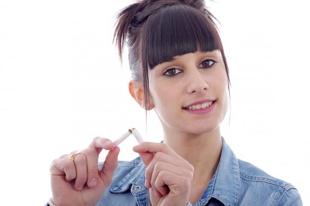 Молодая брюнетка женщина ломает сигарету, концепция не курить