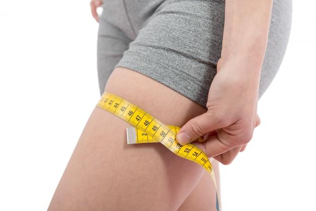 若い女性は彼女の太ももを測定しています