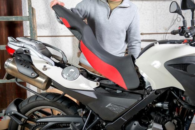 若い男がバイクの修理