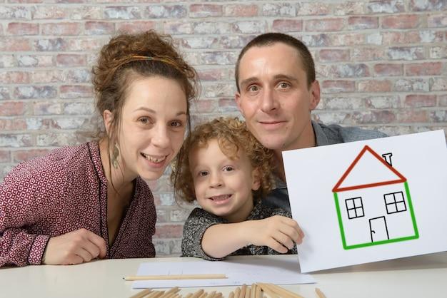Счастливая семья, ребенок держит бумагу с рисунком дома