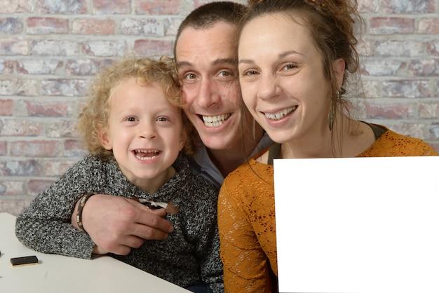 幸せな家族、白い紙のシートを保持しているお母さん
