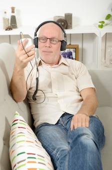 ヘッドフォンで音楽を聞いているハンサムな成熟した男