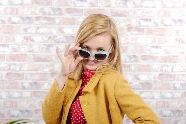 Красивая молодая белокурая женщина с желтой курткой