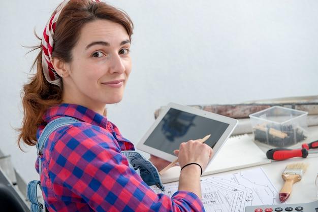 Дизайнер интерьера молодой женщины используя цифровую таблетку