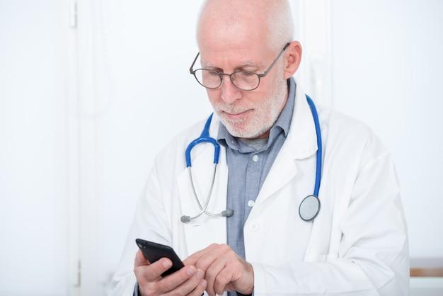 彼のオフィスで電話で成熟した医師