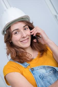 Молодой инженер женщина с защитный шлем, разговаривает по телефону