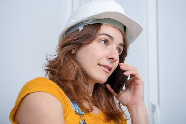 電話で話している安全ヘルメットを持つ若いエンジニアの女性
