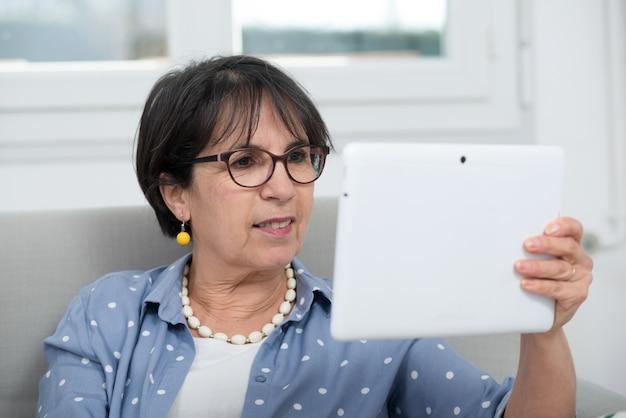 Зрелая брюнетка женщина сидит на диване, с помощью цифрового планшета