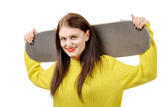 Улыбающийся скейтер девушка держит скейтборд