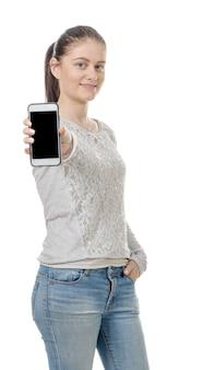 空白のスマートフォンの画面を示す幸せな若い女