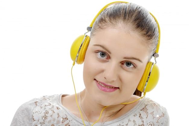 黄色のヘッドフォンで音楽を聴く若い女性
