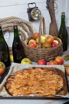 りんごのバスケットとサイダーのボトルとアップルパイ