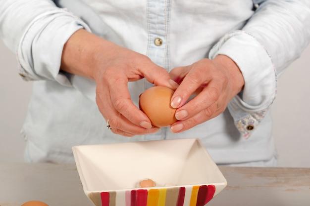 女性の殻の半熟卵の手のクローズアップ