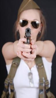 Молодая женщина позирует в военной форме и оружие