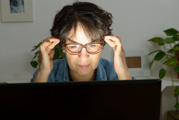 痛みを伴う頭痛に苦しんでいるコンピューターで職場の女性