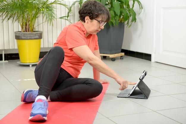 タブレットでフィットネス運動をしている中年の女性
