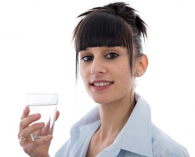 Молодая женщина пьет стакан воды