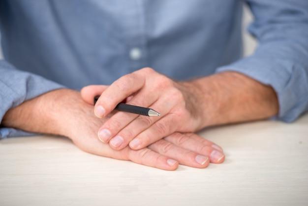 鉛筆で年配の男性の手のクローズアップ