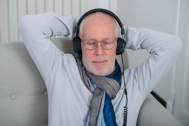 Старший мужчина в наушниках слушает музыку дома