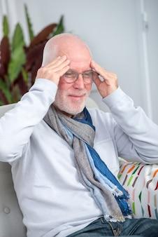 Старший мужчина страдает от головной боли у себя дома