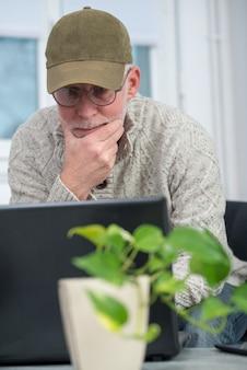 自宅でラップトップを使用してキャップを持つシニア男