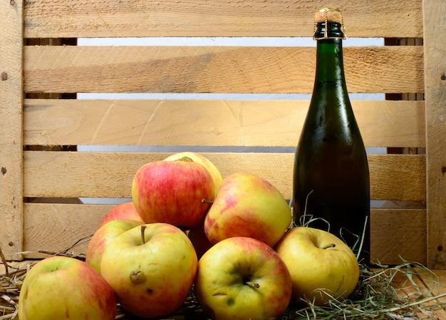Бутылка сидра с яблоками и соломой