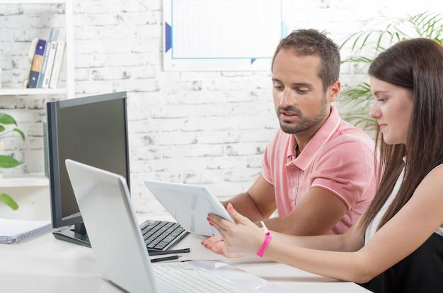 Пара на работе в офисе, молодая женщина с планшета