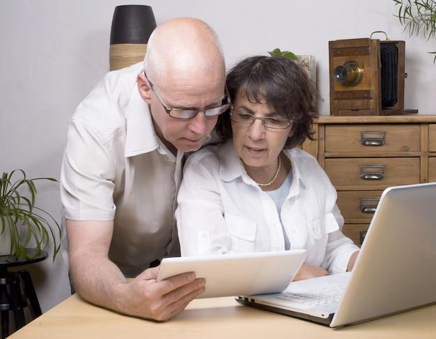Двое пожилых людей играют с планшетным компьютером