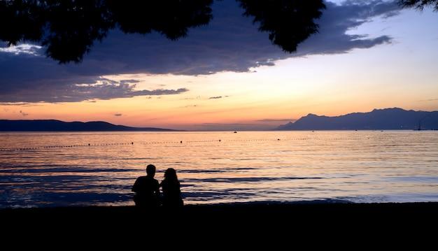 人とビーチの夕日