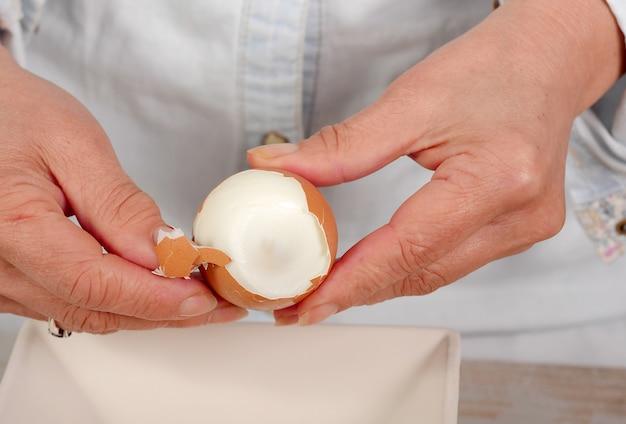 女性の殻のゆで卵の手のクローズアップ