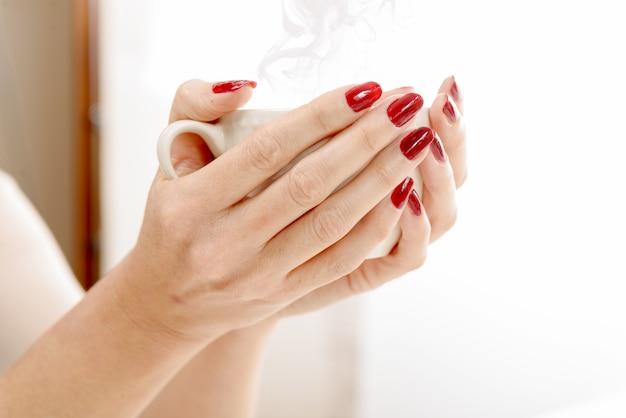 Крупным планом руки молодой женщины с чашкой кофе