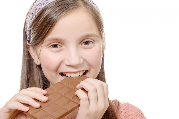 プレティーンの女の子は、白で隔離され、チョコレートを食べる