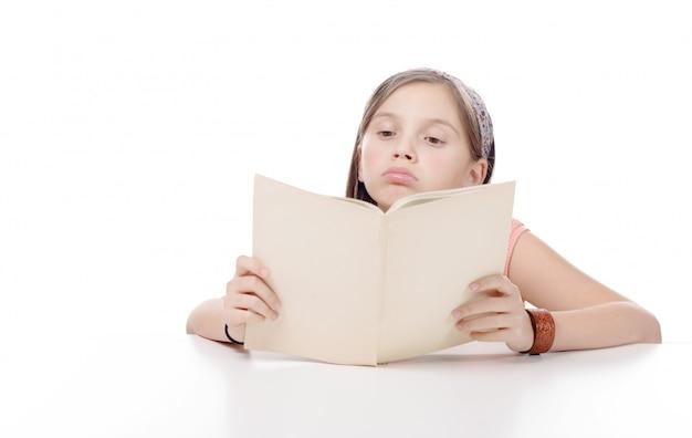 Предподростковая девушка читает книгу, на белом