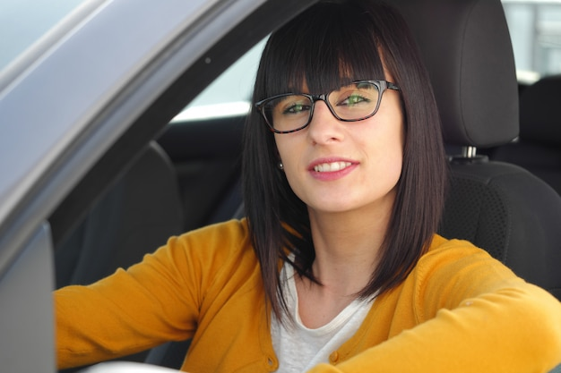 Улыбающаяся женщина сидит в машине