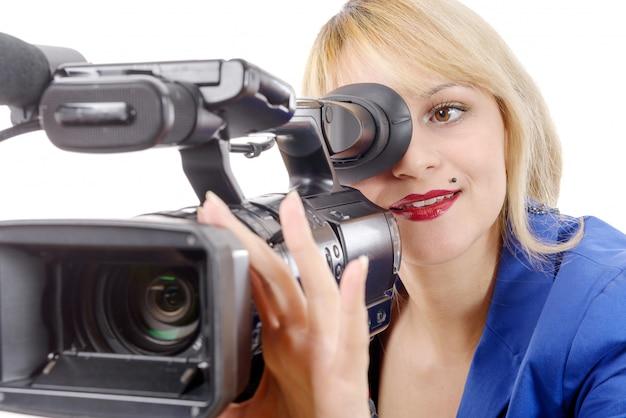 Красивая молодая женщина с голубым костюмом и профессиональной видеокамерой
