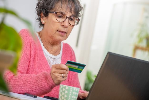 Пожилая брюнетка с покупками в интернете
