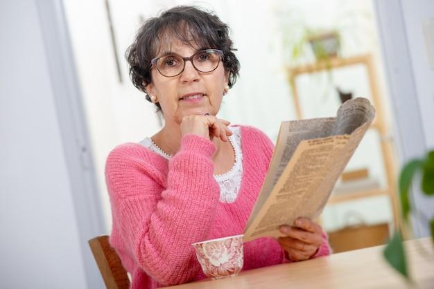 Красивая брюнетка зрелая женщина одевается в розовом, читая газету