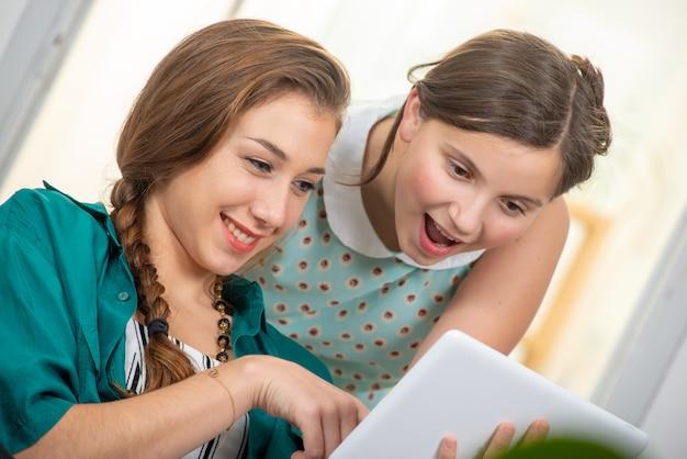 Довольно красивая очаровательная девушка и ее старшая подруга используют планшет