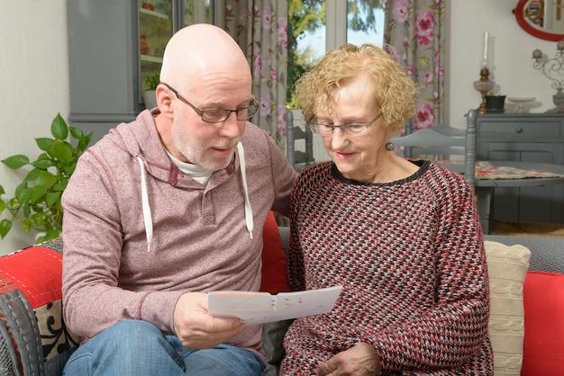 母とソファーで紙を探している大人の息子