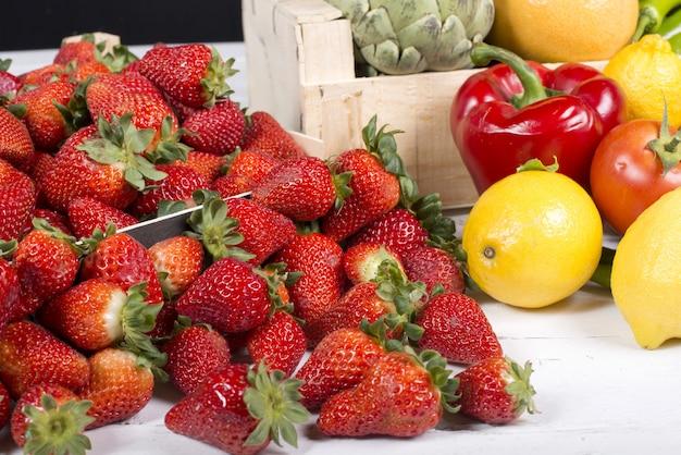 Клубника с фруктами и овощами на столе