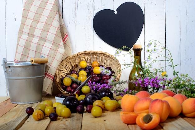 Абрикосы и сливы на деревянном столе с сердцем